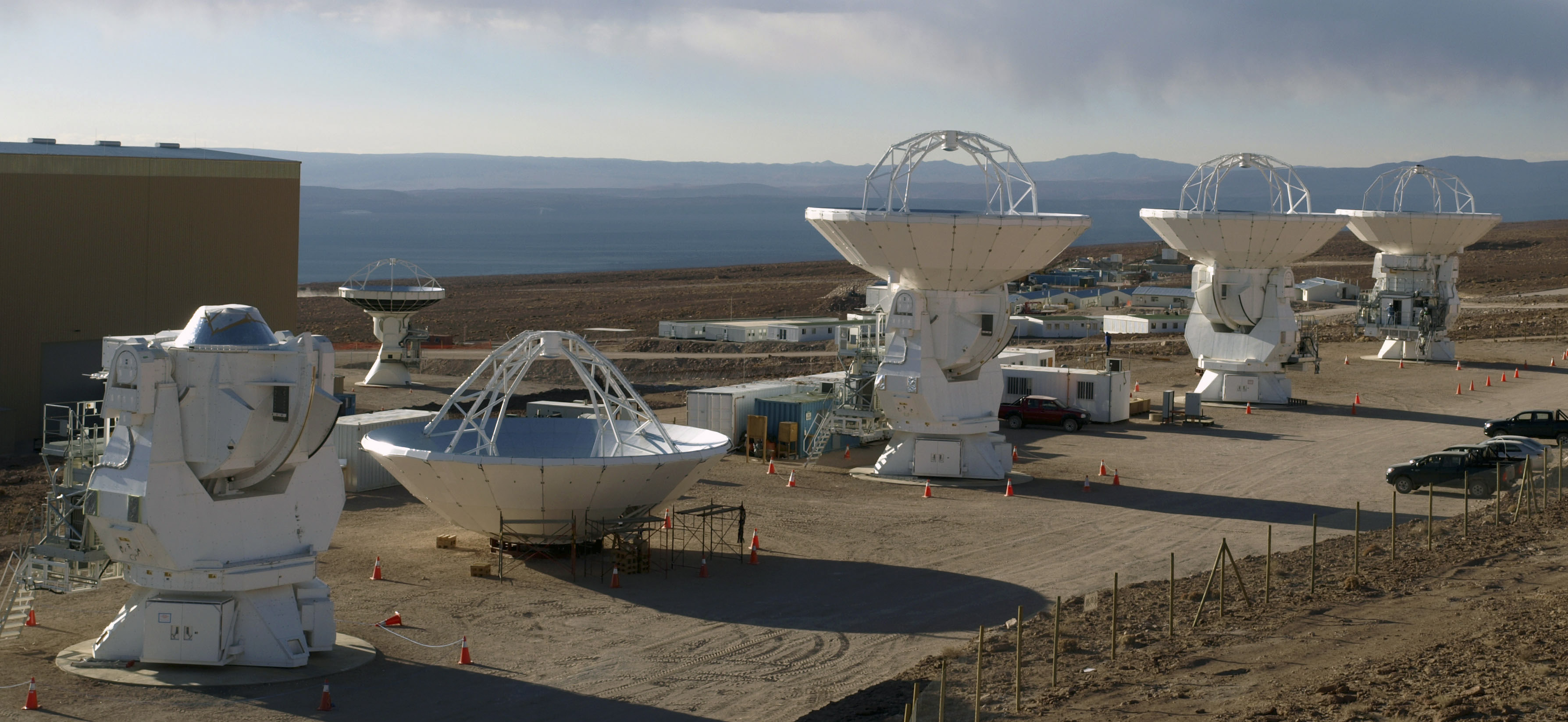 Photo of three completed and one incomplete ALMA antennas.