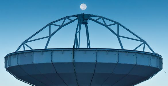 Photo of the full moon above an ALMA radio antenna.