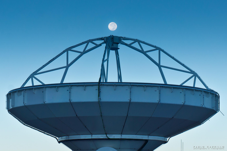 Photo of the full moon above an ALMA radio antenna.