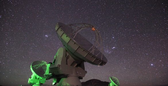 Three ALMA telescopes lit in green, at night with a starry sky.
