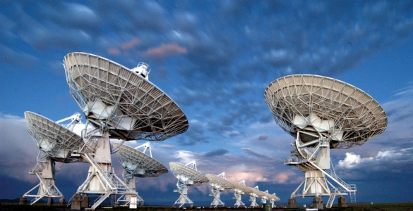 Photo of ten VLA antennas pointing at a cloudy sky at twilight.