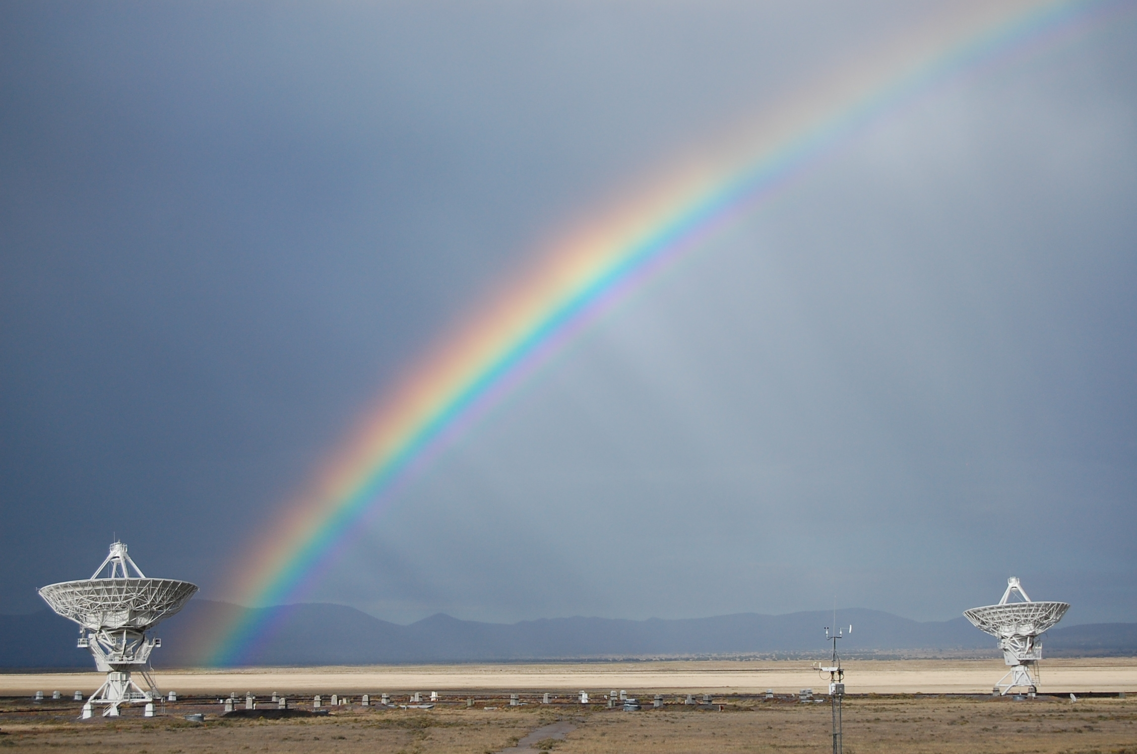 A photo of a rainbow over the VLA telescope in the desert.