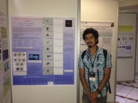 young man standing in front of poster at a conference