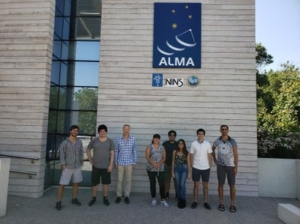group photo of students and scientists in front of Alma and NINS sign
