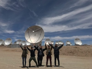 Students with their arms outstretched in front a field of satellite dishes