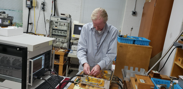 A man with blond hair in a lab coat works on multiple amplifiers.